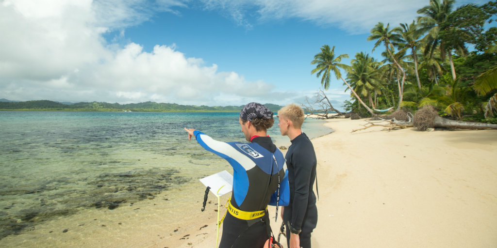 One volunteer pointing out towards the ocean while speaking to another volunteer.