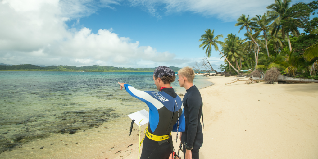 Two volunteers in the marine conservation program surveying the ocean Off of the coast of Caqalai Island, Fiji.