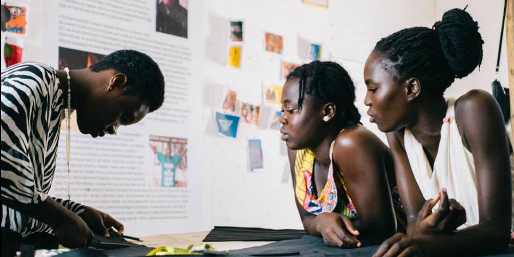 Two Ghanaian women watching a third woman doing a demonstration.