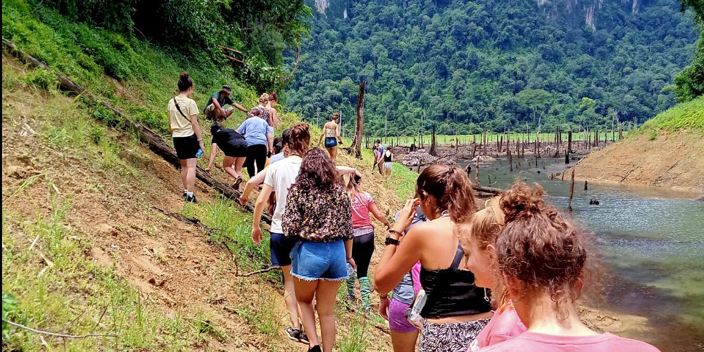 volunteers hiking alongside a river in Phang Nga