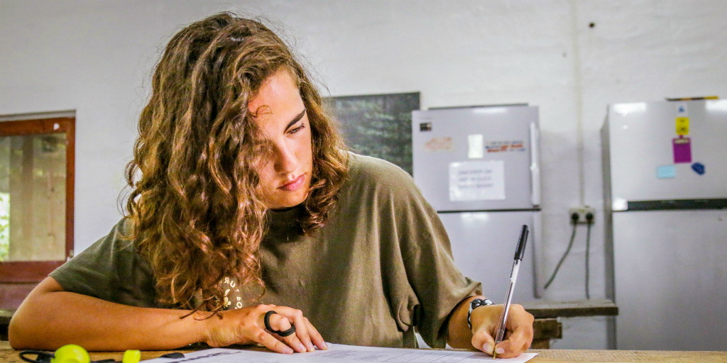 A lady writes notes during her work experience program.