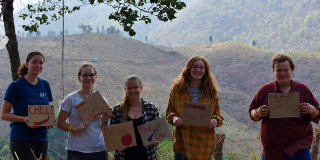 GVI volunteers hold signs of seeds that were planted in the garden.